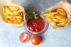 Batatas fritas, batatas fritadas com ketchup e tomates no fundo do granito cinzento-azul fotos de stock