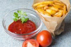 Batatas fritas, batatas fritadas com ketchup e tomates no fundo do granito cinzento-azul imagem de stock
