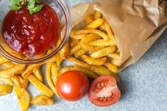Batatas fritas, batatas fritadas com ketchup e tomates no fundo do granito cinzento-azul fotos de stock royalty free