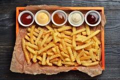Batatas fritas na bandeja de madeira grande com molhos Foto de Stock Royalty Free