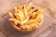 Batatas fritas saborosos na bacia de madeira no guardanapo de serapilheira imagens de stock