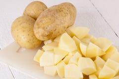 Batatas inteiras e partes desbastadas na placa de corte Fotografia de Stock