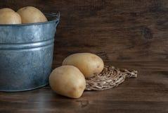Batatas na cubeta do metal no fundo de madeira escuro fotos de stock royalty free
