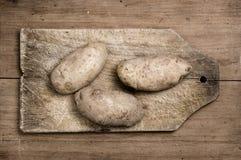 Batatas na tabela velha. Imagens de Stock