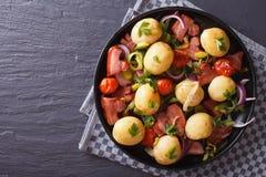 Batatas novas com opinião superior horizontal do bacon, da cebola e do tomate Imagem de Stock