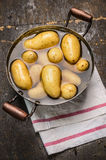 Batatas novas frescas na bandeja velha com água no fundo de madeira rústico Imagens de Stock