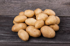 Batatas novas no fim de madeira da tabela acima Fotos de Stock Royalty Free