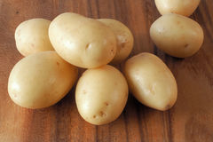 Batatas pequenas em uma placa de corte de madeira Fotos de Stock