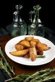 Batatas rústicas em um fundo escuro imagens de stock royalty free