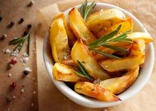 Batatas Roasted com alecrins em uma bacia branca Fotografia de Stock