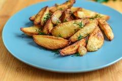 Batatas Roasted com pimenta e cominhos de sal no fundo de madeira Imagens de Stock