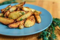 Batatas Roasted com pimenta e cominhos de sal no fundo de madeira Imagem de Stock