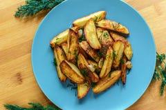 Batatas Roasted com pimenta e cominhos de sal no fundo de madeira Fotografia de Stock Royalty Free