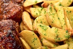 Batatas Roasted com verdes do tempero e duas partes de carne imagens de stock royalty free