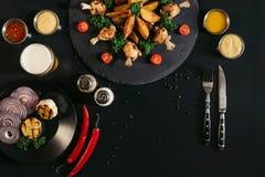 batatas roasted deliciosas com asas de galinha, molhos, vegetais e vidro da cerveja imagem de stock royalty free