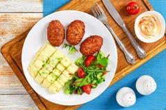 Batatas trituradas polvilhadas com os verdes, costoletas suculentas da carne Imagens de Stock