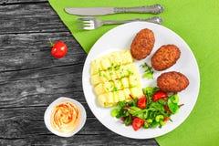 Batatas trituradas polvilhadas com os verdes, costoletas suculentas da carne Fotos de Stock Royalty Free