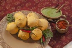 Batate Vada mit Knoblauch und Minzenchutney und -paprikas auf weißer Platte Lizenzfreies Stockbild