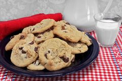 A batch of chocolate chip walnut cookies on a plate with a glass Stock Photos