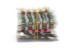Batch of pills packages. Batch of packages of multicolored pills tightened by the elastic band royalty free stock image