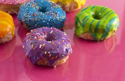 Batch of Rainbow Colored Glazed Donuts. A Batch of Rainbow Colored Glazed Donuts royalty free stock images