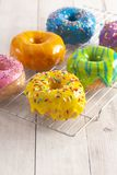 A Batch of Rainbow Donuts on a White Wood Table. Batch of Rainbow Donuts on a White Wood Table stock image