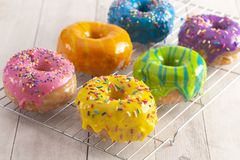 A Batch of Rainbow Donuts on a White Wood Table. Batch of Rainbow Donuts on a White Wood Table stock photography