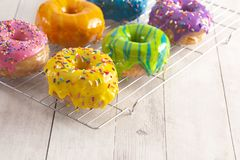 A Batch of Rainbow Donuts on a White Wood Table. Batch of Rainbow Donuts on a White Wood Table royalty free stock image