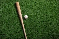 Bate de béisbol y bola en fondo verde del césped Foto de archivo