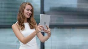Bate-papo video em linha na tabuleta pela menina bonita, escritório exterior