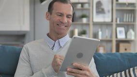 Bate-papo video em linha na tabuleta pelo homem envelhecido médio que senta-se no sofá vídeos de arquivo