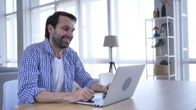 Bate-papo video em linha no portátil no trabalho pelo homem ocasional da barba video estoque
