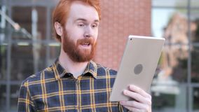 Bate-papo video exterior na tabuleta pelo homem novo da barba do ruivo filme