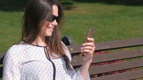Bate-papo video falador da morena da jovem mulher no telefone celular que senta-se no banco no parque filme