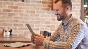 Bate-papo video na tabuleta pelo homem ocasional da barba vídeos de arquivo