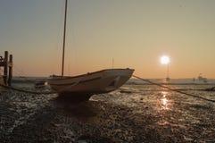 Bateau à marée basse au coucher du soleil Image libre de droits
