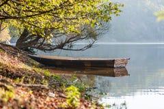 Bateau à rames amarré pour pêcher sur le lac au rivage sous les arbres Thème extérieur Thème des vacances, des vacances, des lois photographie stock libre de droits