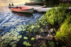 Bateau à rames au rivage de lac au crépuscule Image libre de droits