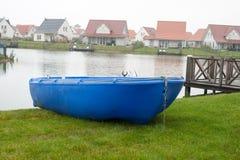 Bateau à rames bleu sur le lac des vacances Photo stock