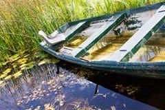 Bateau à rames d'Abdandoned dans un marais photos stock