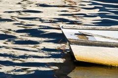 Bateau à rames dans l'eau de fin de l'après-midi avec des réflexions Image libre de droits
