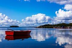 Bateau à rames rouge sur une baie idyllique en Suède Image libre de droits