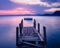 Bateau à rames silhouetté sur le policier de lac, Italie Photographie stock