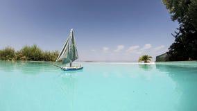 Bateau à voile de jouet flottant dans une piscine Image libre de droits