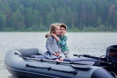 Bateau à voile de meilleur ami du ` s de fille et de garçon sur le lac par jour d'été Photos stock