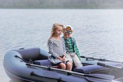 Bateau à voile de meilleur ami du ` s de fille et de garçon sur le lac par jour d'été Images stock