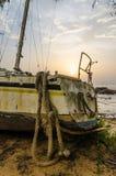 Bateau à voile ou yacht abandonné s'étendant sur la plage dans Kribi, Cameroun pendant le coucher du soleil, Afrique Photo libre de droits