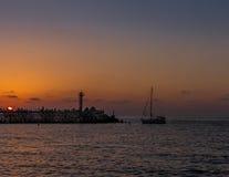 Bateau à voile retournant au coucher du soleil Images stock