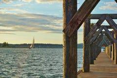 Bateau à voile sur le lac passant par le dock en bois Images libres de droits