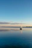 Bateau à voile sur un lac calme avec la réflexion Image stock